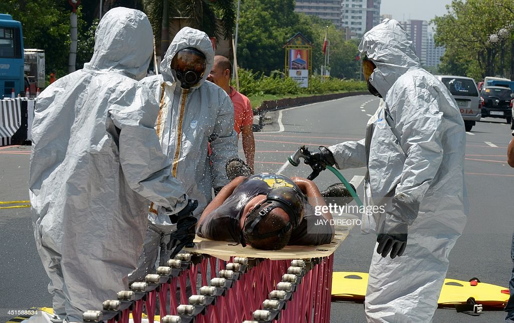 Rescuers in chemical suits decontaminate a mock victim during an earthquake drill on July 2 2014 The National Disaster Risk Reduction and Management...