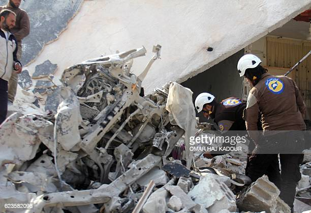 TOPSHOT Rescuers inspect a destroyed building in the Syrian village of Kfar Jales on the outskirts of Idlib following air strikes by Syrian and...