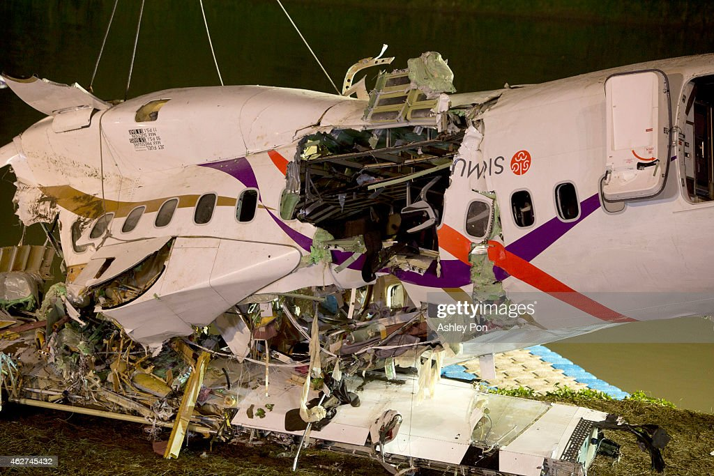Rescuers lift the wreckage of the TransAsia ATR 72600 oot of the Keelung river at New Taipei City on February 4 2015 At least 23 people were killed...