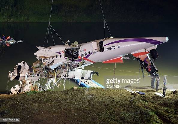 Rescuers lift the wreckage of the TransAsia ATR 72600 out of the Keelung river at New Taipei City on February 4 2015 At least 23 people were killed...