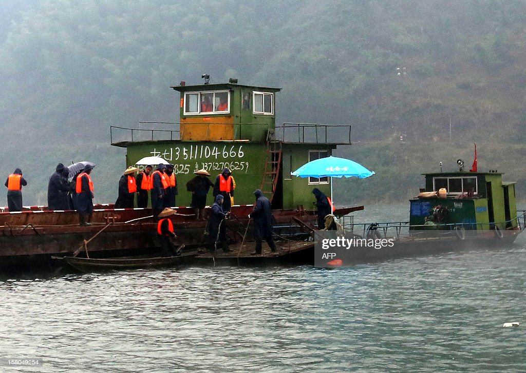 Rescuers look for a flat-bottomed cargo boat which capsized in waters near Pingshan village in Anhua county, central China's Hunan province on December 10, 2012. Eight people have been confirmed missing after the accident on December 9. Four trucks that the boat was transporting went down with the boat local authorities said. CHINA OUT AFP PHOTO