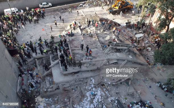 TOPSHOT Rescuers look for survivors in a multistory building flattened by a powerful quake in Mexico City on September 19 2017 A devastating quake in...