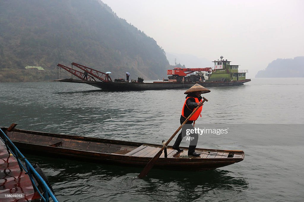 Rescuers look for survivors of a flat-bottomed cargo boat which capsized in waters near Pingshan village in Anhua county, central China's Hunan province on December 10, 2012. Eight people have been confirmed missing after the accident on December 9. Four trucks that the boat was transporting went down with the boat local authorities said. CHINA OUT AFP PHOTO