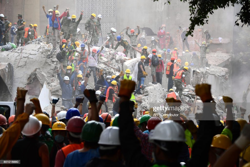TOPSHOT - Rescuers make the signal for silence during the search for survivors in a flattened building in Mexico City on September 21, 2017, two days after a strong quake hit central Mexico killing at least 240 people. A powerful 7.1 earthquake shook Mexico City on Tuesday, causing panic among the megalopolis' 20 million inhabitants on the 32nd anniversary of a devastating 1985 quake. /