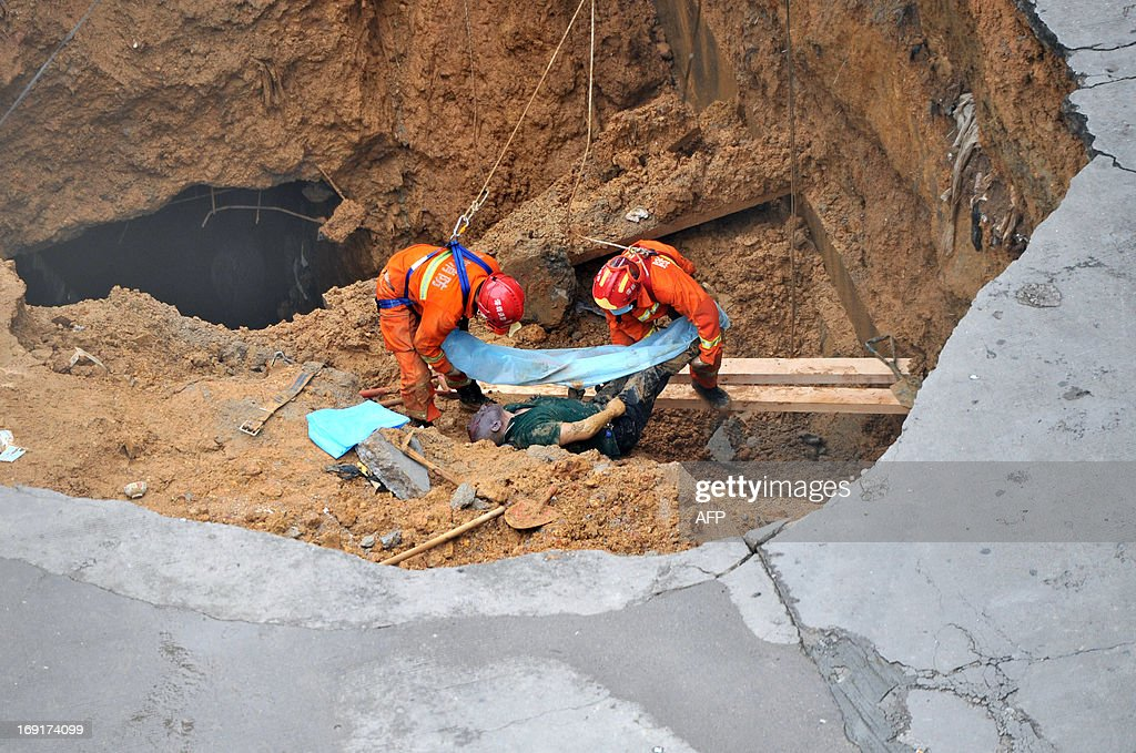Rescuers move a dead body found in a sinkhole on a road in Shenzhen, south China's Guangdong province on May 21, 2013. Five people died when a 10 metre (33 feet) wide sinkhole opened up at the gates of an industrial estate in Shenzhen, the southern Chinese boom town neighbouring Hong Kong, local authorities said on May 21. CHINA