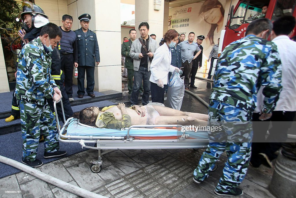 Rescuers move a survivor on a stretcher from a hotel that caught fire in Xiangyang, central China's Hubei province on April 14, 2013. The fire, started from an Internet cafe downstairs, resulted in 11 deaths and 50 injuries, local government reports annouced. CHINA OUT AFP PHOTO