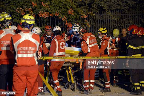 Rescuers of the Italian Red Cross carry the body of a victim on a stretcher in a delimited area in the central Italian village of Amatrice on August...