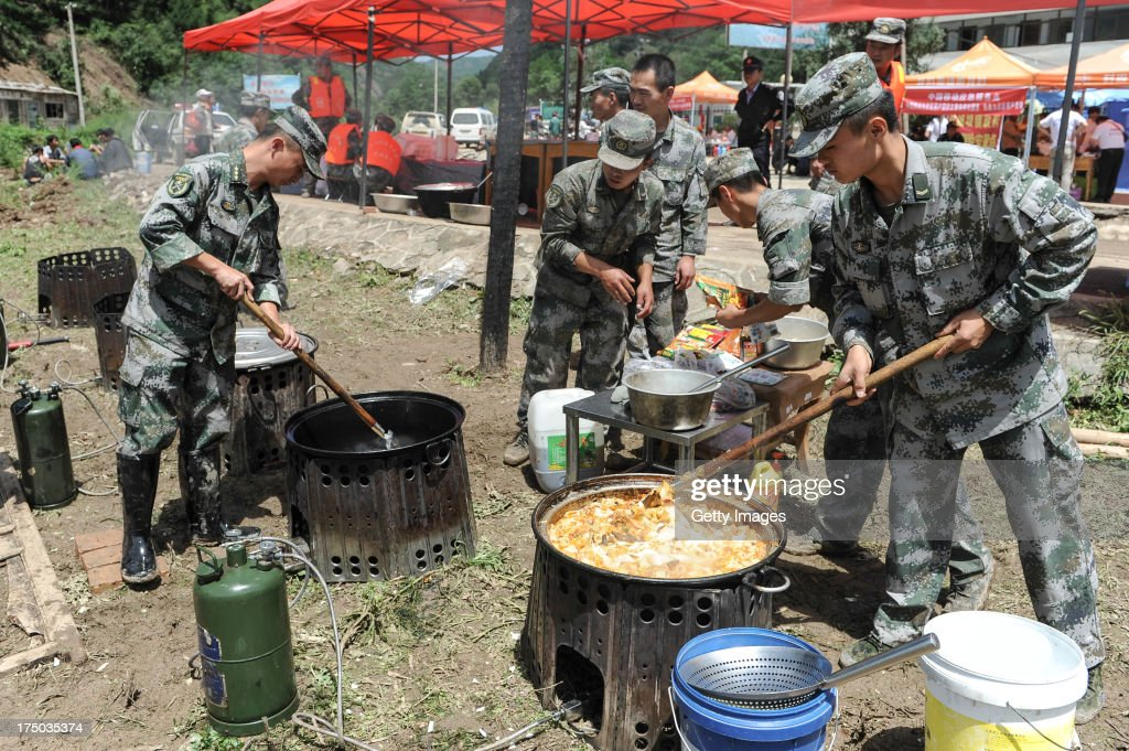 Rescuers prepare a meal at a shelter on July 29, 2013 in Tianshui, China. At least 24 people were killed, with one person still missing, after rainstorm-triggered floods and landslides hit many areas of Tianshui city recently.