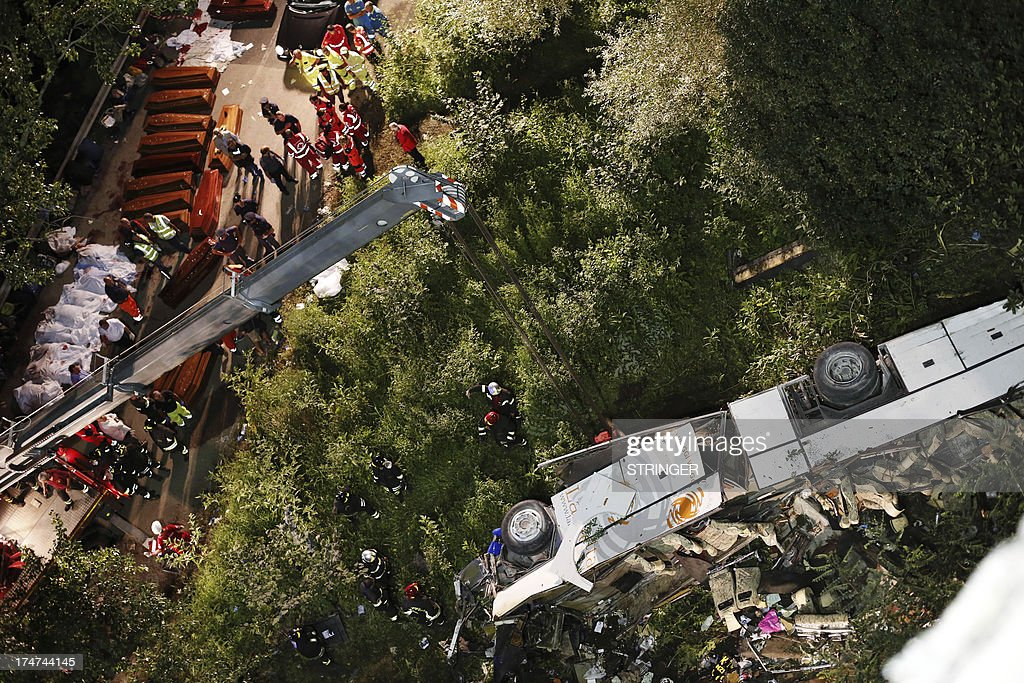 Rescuers prepare the coffins of victims of a bus crash on July 28, 2013 on the road between Monteforte Irpino and Baiano, southern Italy. At least 36 people were killed and several more injured after a coach carrying pilgrims plunged off a motorway flyover in southern Italy, rescue services said. AFP PHOTO / STINGER / AGENZIA CONTROLUCE