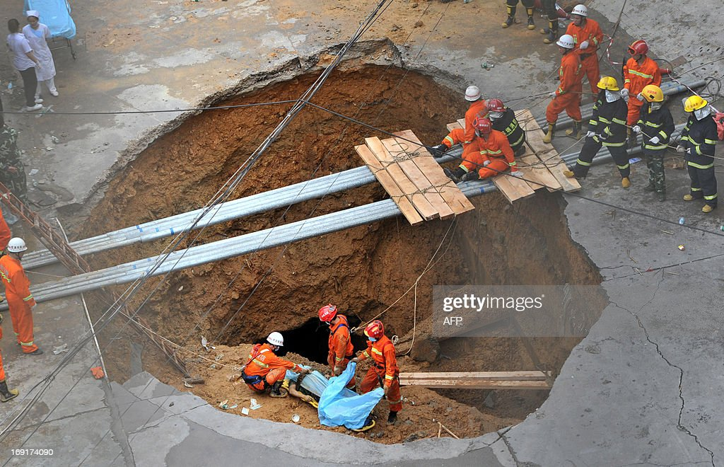 Rescuers prepare to move a dead body found in a sinkhole on a road in Shenzhen, south China's Guangdong province on May 21, 2013. Five people died when a 10 metre (33 feet) wide sinkhole opened up at the gates of an industrial estate in Shenzhen, the southern Chinese boom town neighbouring Hong Kong, local authorities said on May 21. CHINA