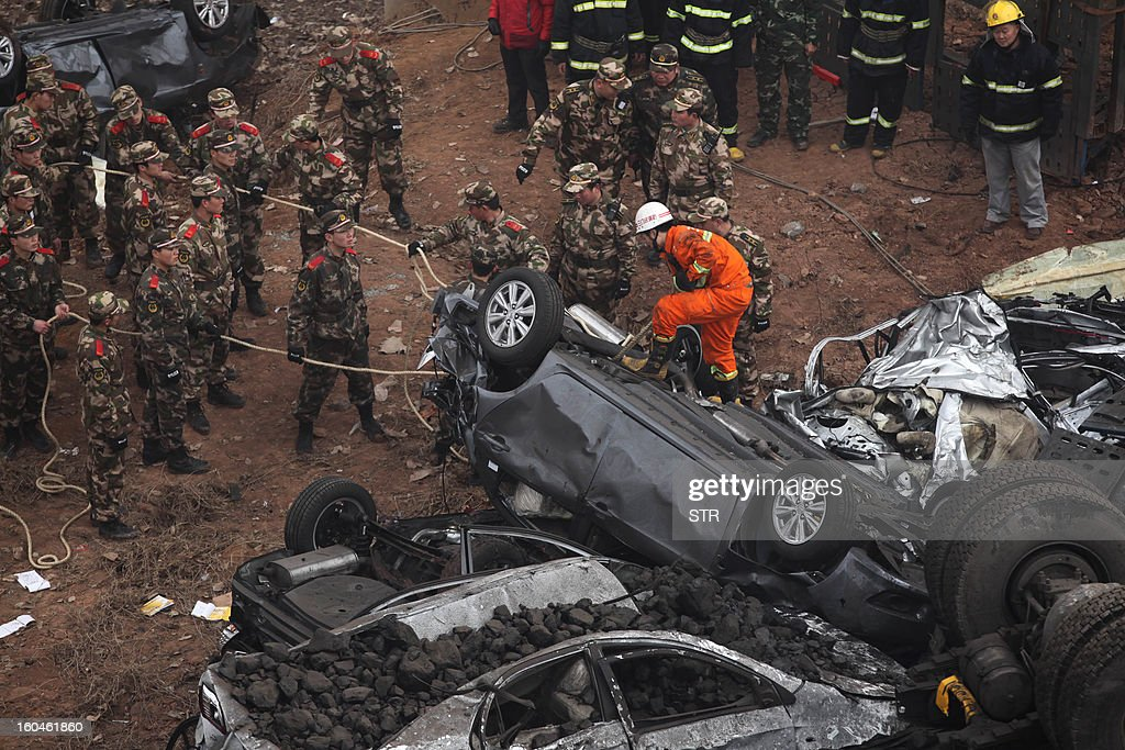 Rescuers pull a damaged car at the scene of the collapsed Yichang bridge near the city of Sanmenxia, central China's Henan province, on February 1, 2013 after a fireworks-laden truck exploded as it crossed the bridge killing 26 people as the structure collapsed and vehicles plummeted to the ground, state-run media reported. An 80-metre long part of the bridge collapsed and six vehicles had been retrieved from the debris, China's official news agency Xinhua said. The bridge near the city of Sanmenxia is on the G30 expressway, the longest road in China, which stretches for nearly 4,400 kilometres (2,700 miles) from China's western border with Kazakhstan to the eastern Yellow Sea.