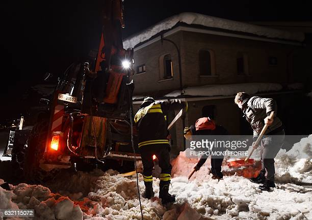 Rescuers remove snow on a road to the village of Penne after an avalanche engulfed a mountain hotel in earthquakeravaged central Italy on January 19...