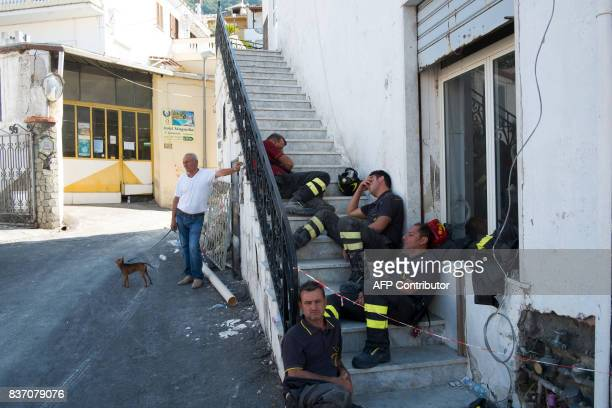 Rescuers rest on steps in Casamicciola Terme on the Italian island of Ischia on August 22 after an earthquake hit the popular Italian tourist island...