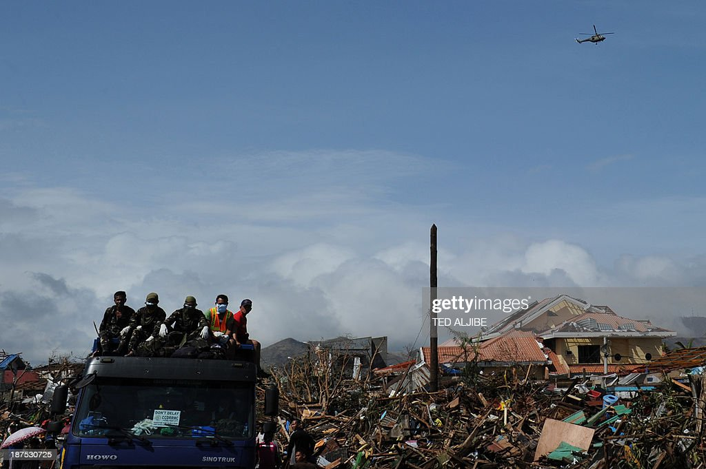 Rescuers (L) ride on a truck as they pass by destroyed houses and debris along a road in Tacloban, on the eastern island of Leyte on November 10, 2013 after Super Typhoon Haiyan swept over the Philippines. The typhoon that destroyed entire towns across the Philippines is believed to have killed more than 10,000 people, authorities said on November 10, which would make it the country's deadliest recorded natural disaster. AFP PHOTO/TED ALJIBE