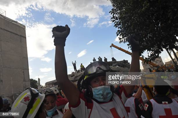 Rescuers rise their clenched fists asking for silence to be able to hear the voices of possible survivors buried under the rubble and debris of...
