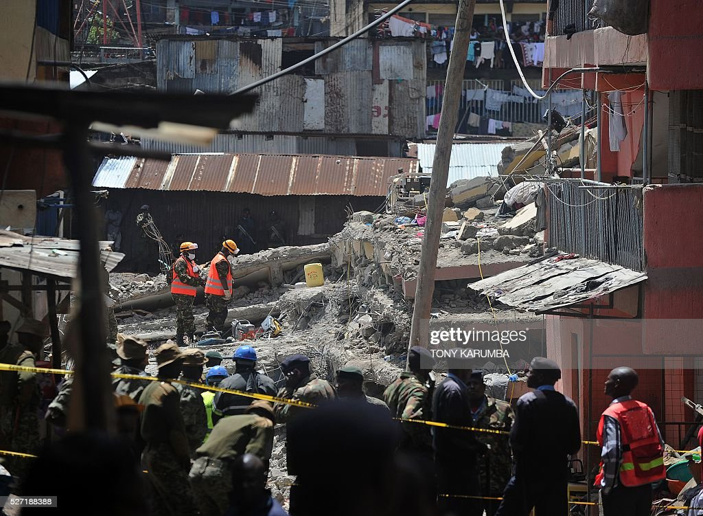 Rescuers search for bodies trapped in rubble on May 2, 2016 at the scene of a collapsed residential building in the low-income suburb of Huruma in Nairobi. The death toll in the collapse of a six-storey building in Nairobi on April 29 rose to 21 on May 2 after four more bodies were pulled from the rubble of the residential structure that gave way during weekend storms. / AFP / TONY