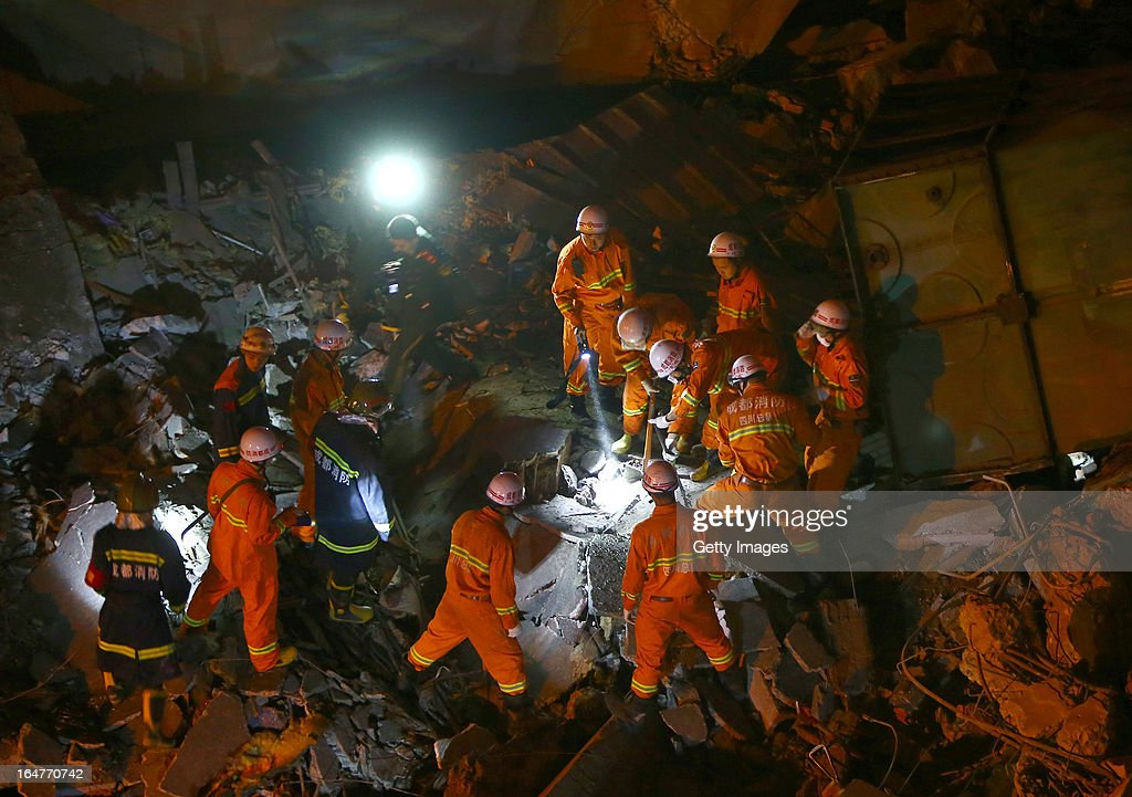 Rescuers search for buried people after a three-storey building collapsed on March 27, 2013 in Chengdu, China. The building in the process of demolition collapsed suddenly at around 6 p.m. on Wednesday, and the number of casualties remains unclear.