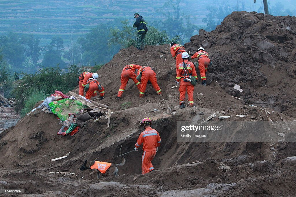 Rescuers search for buried people at the site of a mudslide at Yongguang village on July 23, 2013 in Minxian, China. At least 95 people were killed and more than 1,000 people injured after a 6.6-magnitude earthquake jolted the border of Minxian county and Zhangxian county in Gansu province on Monday morning.