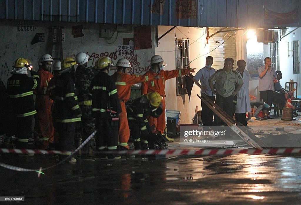 Rescuers search for people buried in a road cave-in accident site on May 21, 2013 in Shenzhen, China. Three people have been confirmed dead and two others injured after a road collapse engulfed five passers-by in Longgang district of Shenzhen city at around 9.00 pm local time Monday.