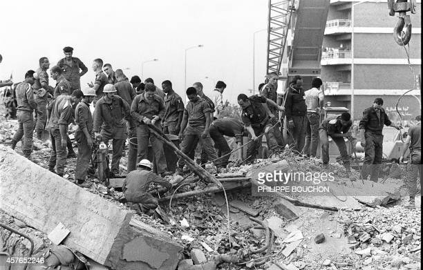 Rescuers search for survivors 25 October 1983 in Beirut through the rubble of the Drakkar building which was destroyed by a suicide truck bomber...