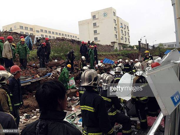 Rescuers search for survivors after a retaining wall at a factory collapsed killing 18 people while three others were injured at the Huangdao...