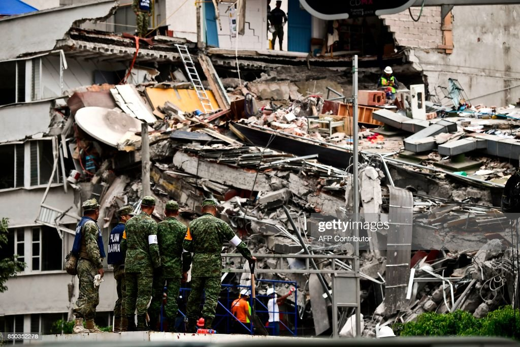 TOPSHOT - Rescuers search for survivors amid the rubble from a building flattened by the 7.1-magnitude quake the day before, in Mexico City, on September 20, 2019. Rescuers frantically searched Wednesday for survivors of a powerful earthquake that killed more than 200 people in Mexico on the anniversary of another massive quake that left thousands dead and still haunts the country. /