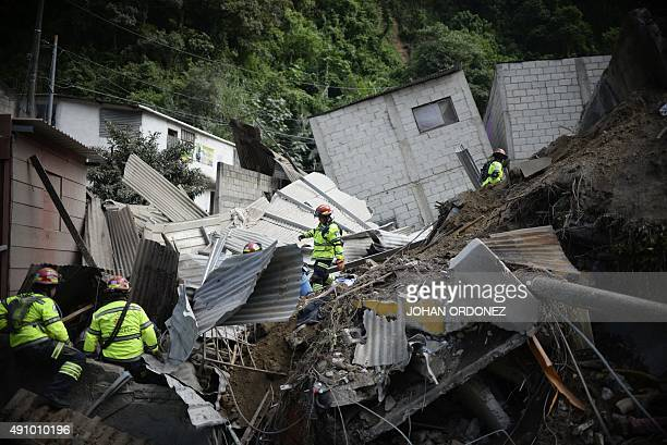 Rescuers search for victims after a landslide at Cambray village in Santa Catarina Pinula municipality Guatemala on October 2 2015 The landslide...