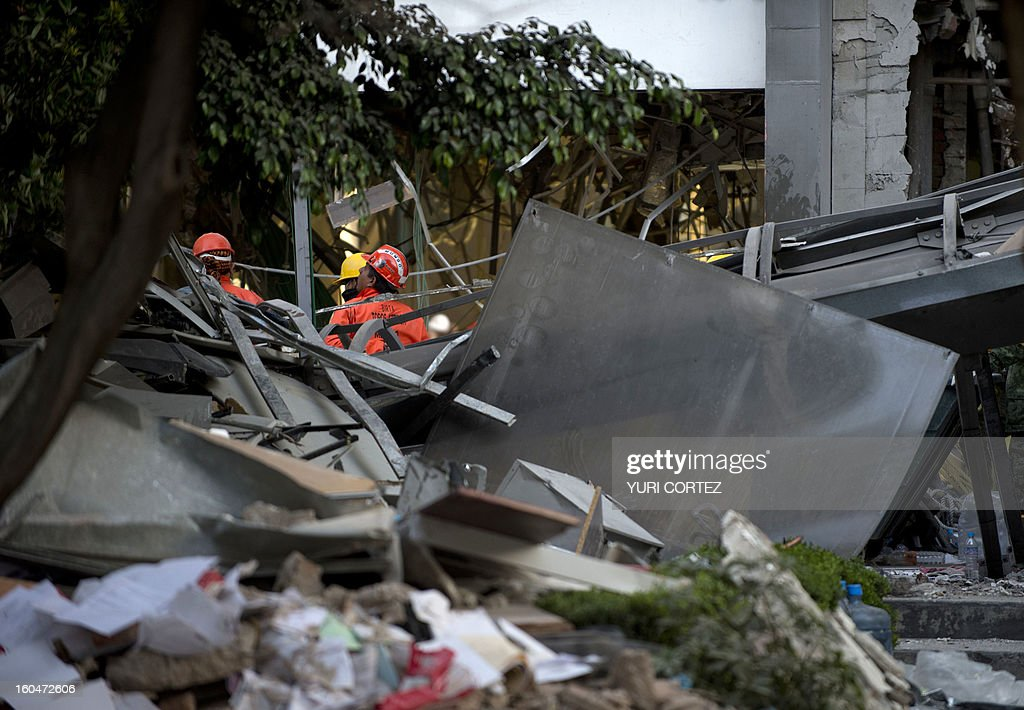 Rescuers search for victims amid the debris at the headquarters of the state-owned Mexican oil giant Pemex in Mexico City on February 1, 2013, following a blast inside the building. An explosion rocked the skyscraper, leaving up to now 25 dead and 100 injured, as a plume of black smoke billowed from the 54-floor tower, according to official sources.
