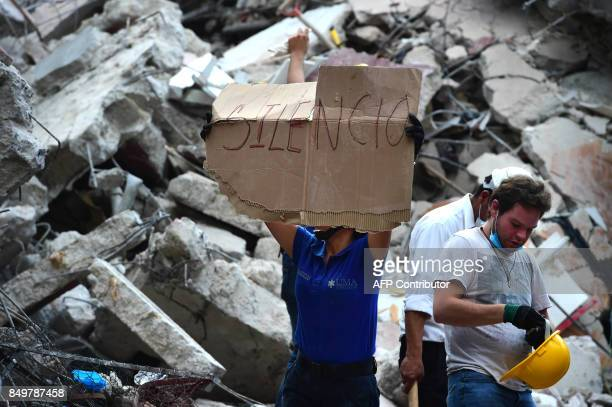 TOPSHOT Rescuers searching for survivors buried under the rubble and debris of a building flattened by a 71magnitude quake ask for silence in Mexico...