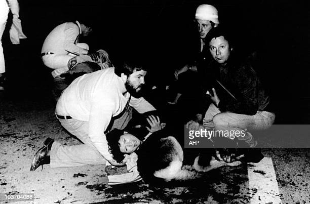 Rescuers secure wounded woman and her dog at the place where a bomb hidden in a rubbish bin exploded just after 10pm on Saturday 26 September 1980...