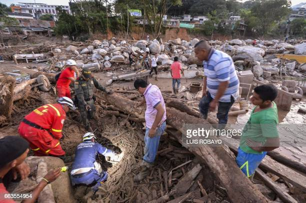 TOPSHOT Rescuers seek people among the rubble left by mudslides following heavy rains in Mocoa Putumayo department southern Colombia on April 1 2017...