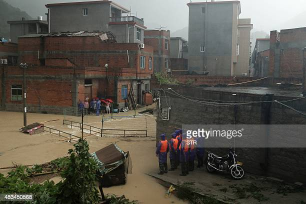 Rescuers stand by a flooded area as Typhoon Soudelor brought heavy rain to Ningde eastern China's Fujian province on August 9 2015 A weakened Typhoon...