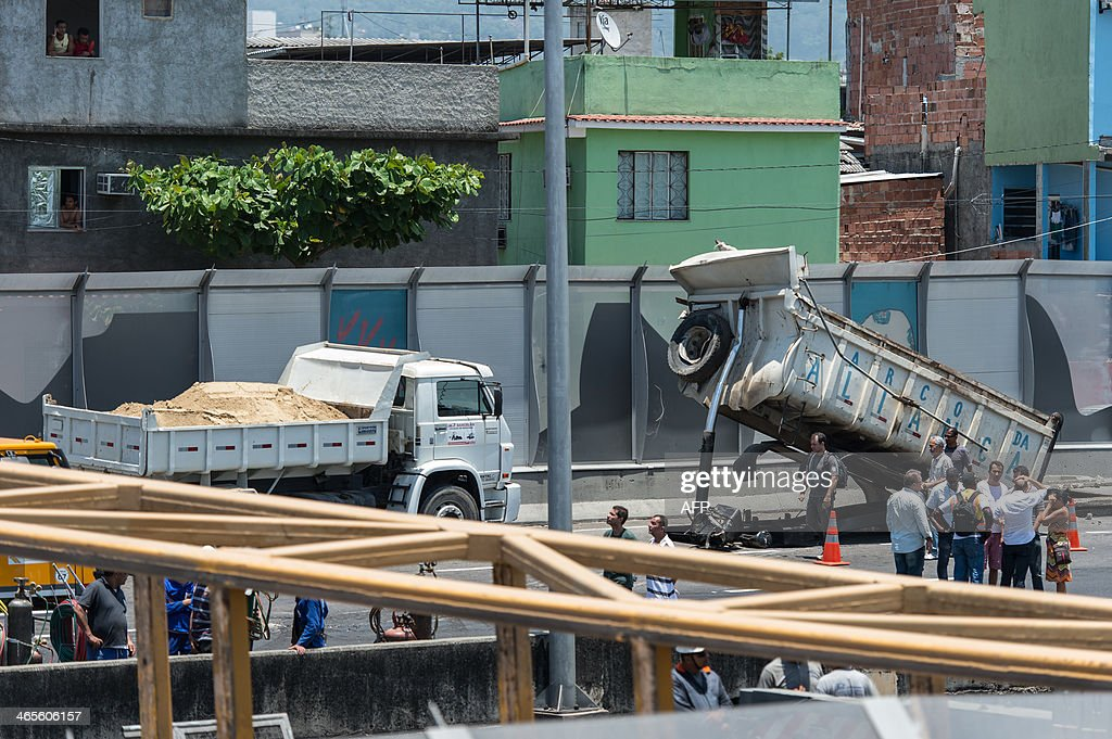 Rescuers stand by the bed of a truck that hit a pedestrian bridge over the Linha Amarela (the yellow line) road in Rio de Janeiro, Brazil, on January 28, 2014. A pedestrian overpass spanning a busy road in Rio de Janeiro collapsed after being struck by a truck on Tuesday, killing four people below, officials said. At least four people were also injured in the accident. A pedestlian bridge falls on a taxi after a truck hit the bridge on the yellow line expressway in Rio de Janeiro, Brazil on January 28, 2014. 2014.
