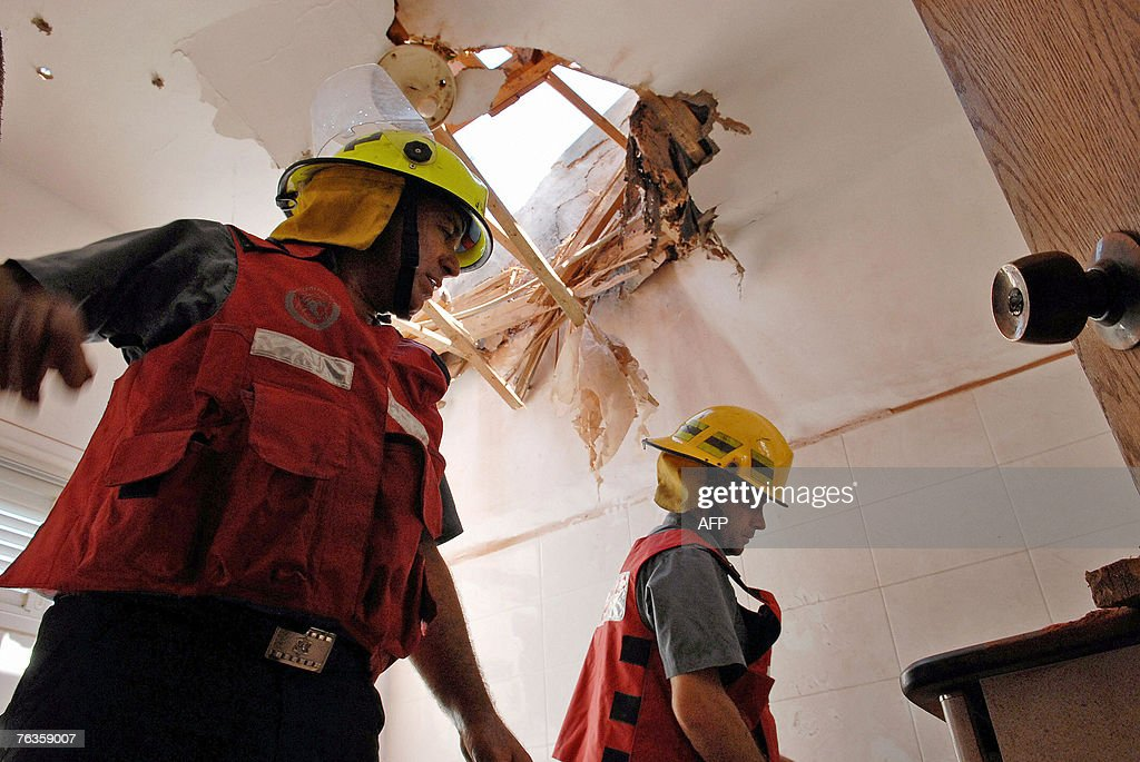 Rescuers stand in the bathroom of a home hit by a home-made Qassam rocket in the southern Israeli town of Sderot 28 August 2007. The Qassam rocket, fired by militants from the near by Gaza Strip struck the home damaging the roof. One person was injured in the attack, several others suffered from shock. AFP PHOTO / ALMOG SUGAVKER