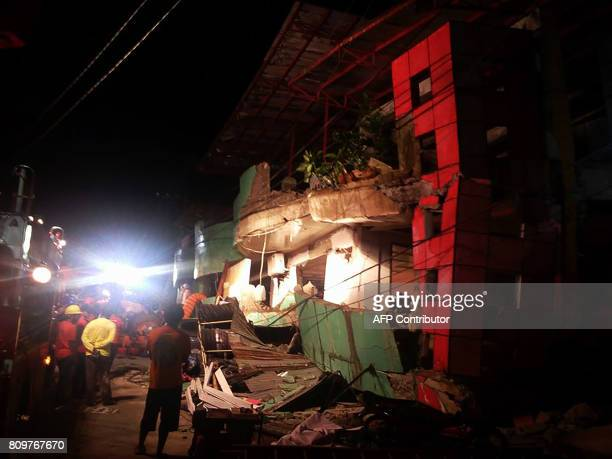 Rescuers stand next to a destroyed building after a 65magnitude earthquake hit the town of Kananga Leyte province in central Philippines on July 6...