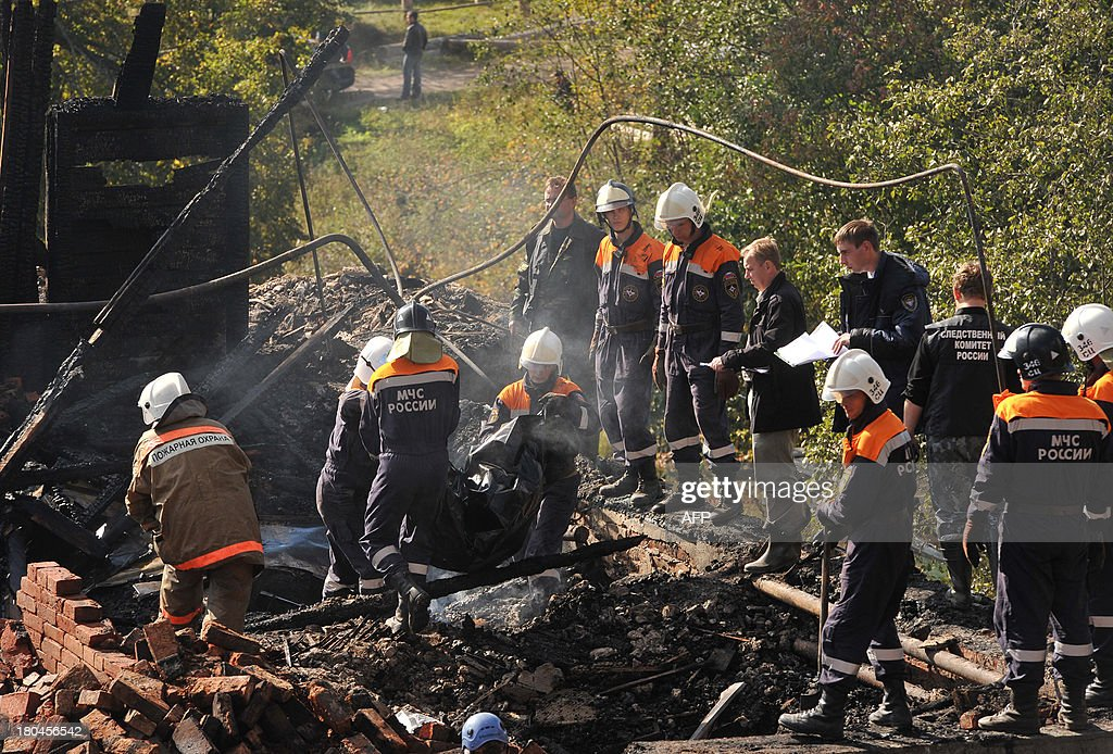 Rescuers take away a body bag with a victim of a fire near the charring remains of a burned out psychiatric hospital in the village of Luka in the northwest Russian Novgorod region on September 13, 2013. Thirty seven people were killed when a fire swept through a wooden psychiatric hospital in northwest Russia overnight yesterday, regional investigators said. AFP PHOTO / OLGA MALTSEVA