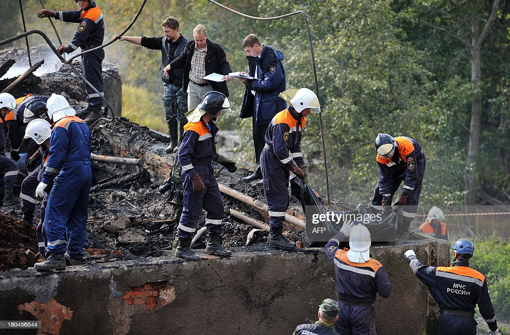 Rescuers take away a body bag with a victim of a fire near the charring remains of a burned out psychiatric hospital in the village of Luka in the northwest Russian Novgorod region on September 13, 2013. Thirty seven people were killed when a fire swept through a wooden psychiatric hospital in northwest Russia overnight yesterday, regional investigators said.