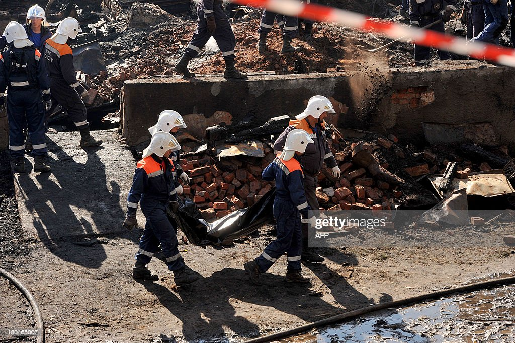 Rescuers take away a body bag with a victim of a pre-dawn fire from the charred remains of the burned out psychiatric hospital in the village of Luka in the northwest Russian Novgorod region, 220 kilometres (137 miles) southeast of Saint Petersburg, on September 13, 2013. Thirty seven people were killed when a fire swept through a wooden psychiatric hospital in northwest Russia overnight yesterday, regional investigators said.