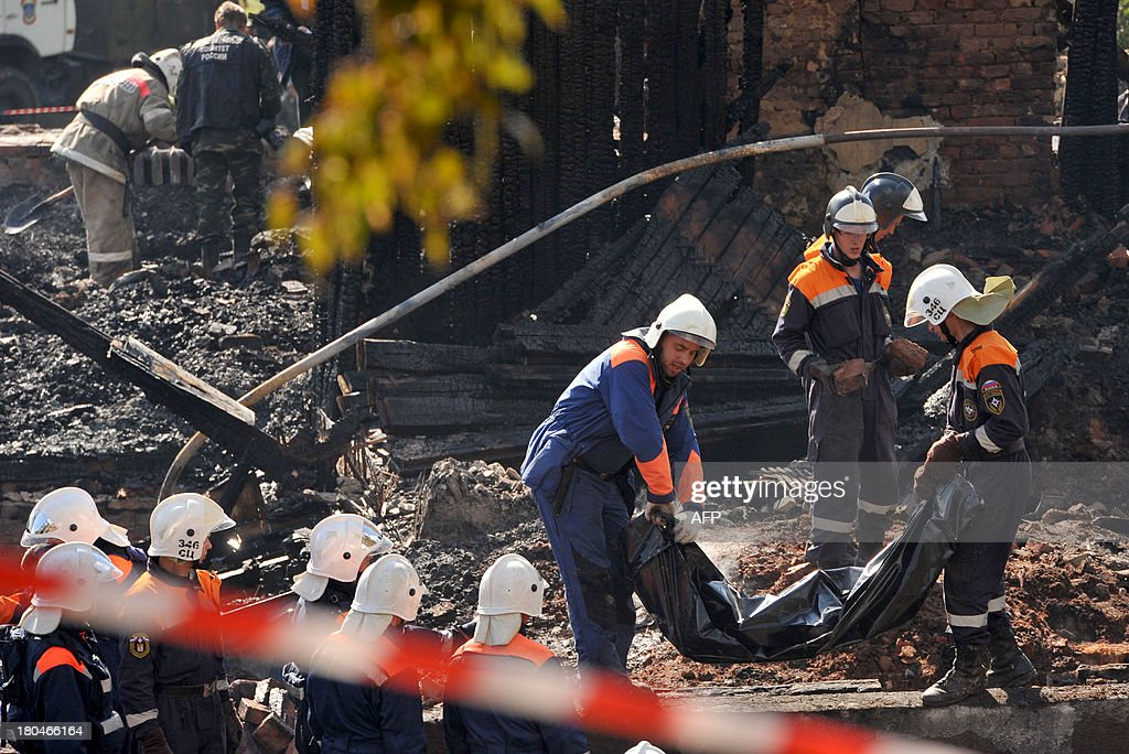 Rescuers take away a body bag with a victim of a pre-dawn fire from the charred remains of the burned out psychiatric hospital in the village of Luka in the northwest Russian Novgorod region, 220 kilometres (137 miles) southeast of Saint Petersburg, on September 13, 2013. Thirty seven people were killed when a fire swept through a wooden psychiatric hospital in northwest Russia overnight yesterday, regional investigators said. AFP PHOTO / OLGA MALTSEVA
