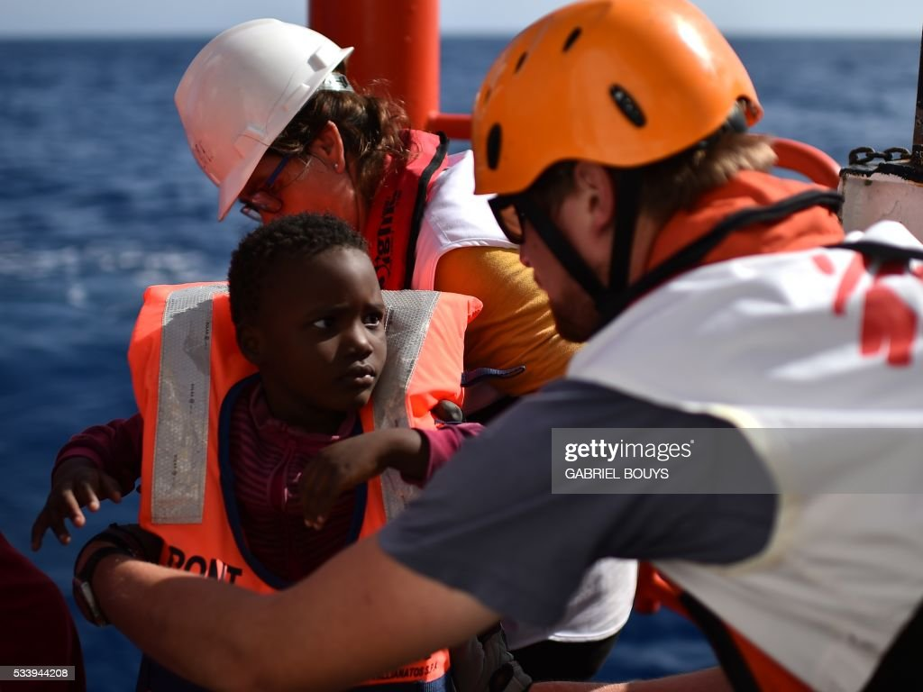 Rescuers take care of a child during a rescue operation at sea of migrants and refugees with the Aquarius, a former North Atlantic fisheries protection ship now used by humanitarians SOS Mediterranee and Medecins Sans Frontieres (Doctors without Borders), on May 24, 2016 in the Mediterranean sea in front of the Libyan coast. / AFP / GABRIEL