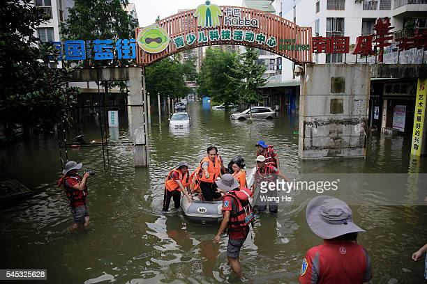 Rescuers take residents to safe place by inflatable boat on July 7 2016 in South Lake Community of Wuhan Hubei Province of China on July 7 2016 in...