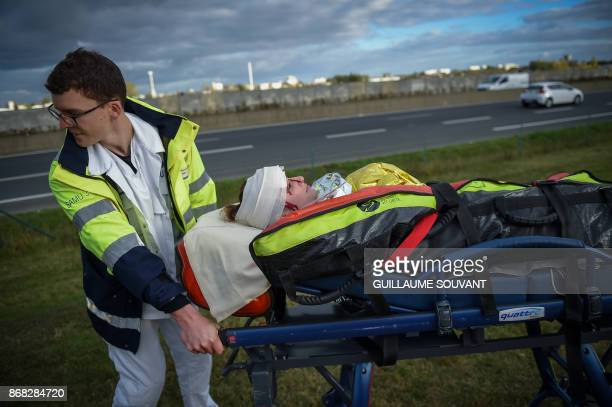 A rescuers takes care of a victim as he pushes a stretcher during an exercise simulating a terrorist attack inside the theatre Espace Malraux in...