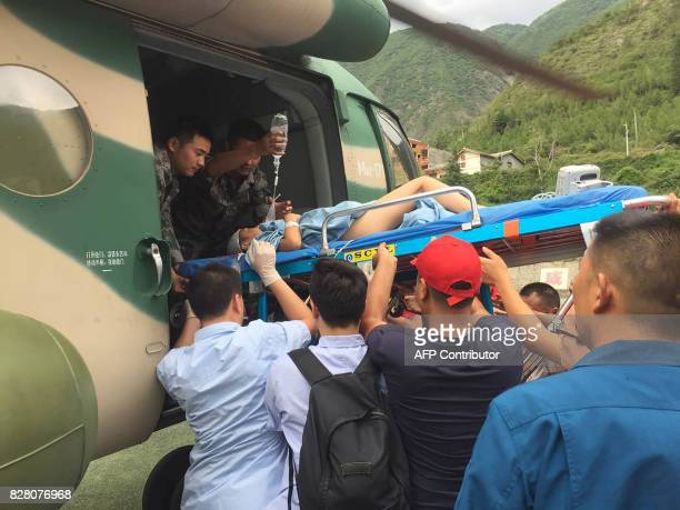Rescuers transfer a survivor injured during an earthquake by a helicopter to Sichuan Provincial People's Hospital in Jiuzhaigou in China's...