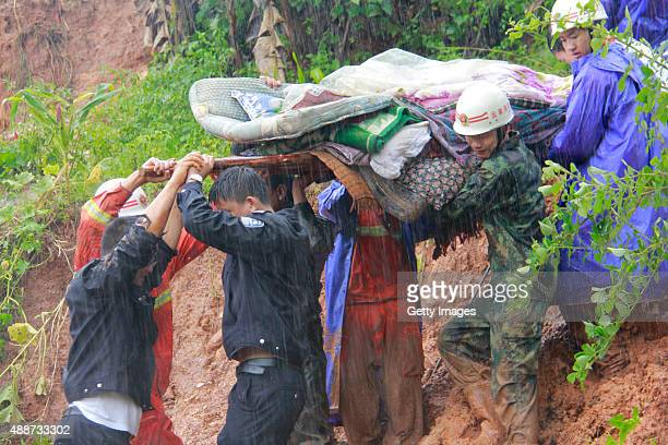 Rescuers transfer trapped residents after a mudslide was caused by a heavy rainstorm on September 16 2015 in Kunming China Torrential rain hit south...