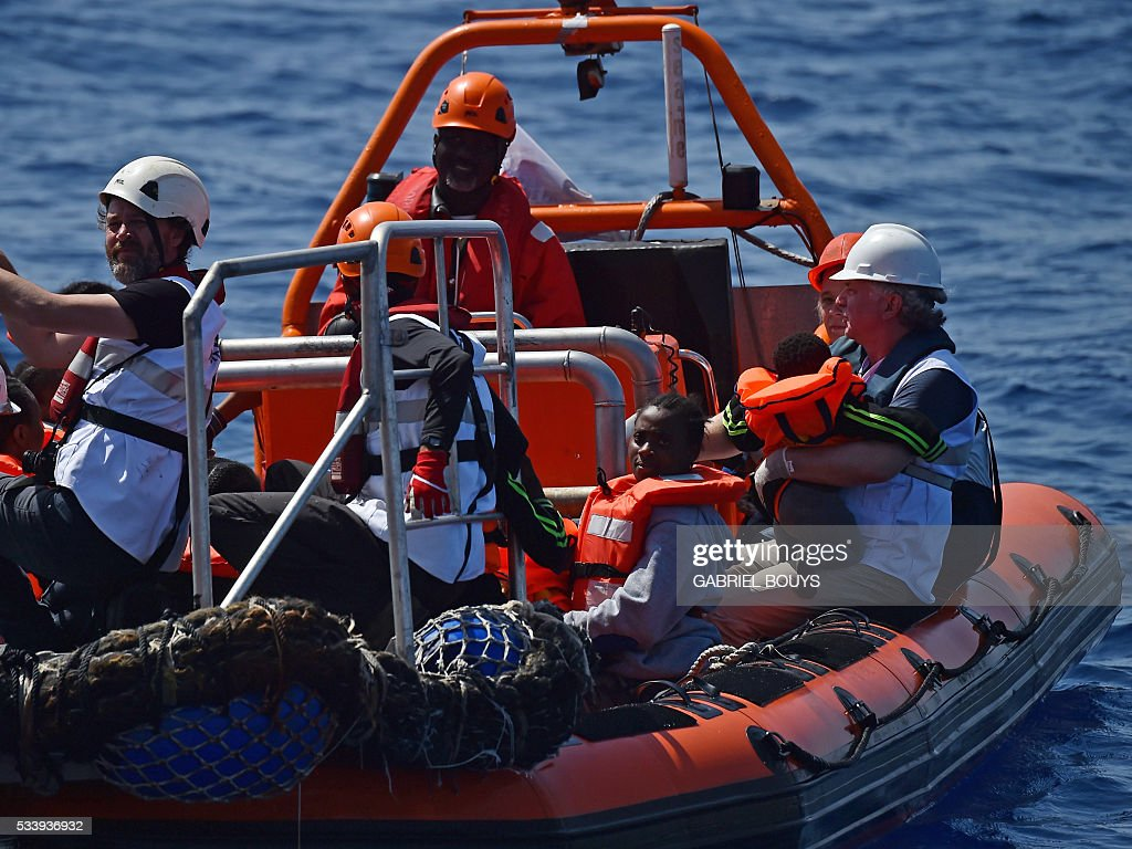 Rescuers transport refugees and migrants during an operation at sea with the Aquarius, a former North Atlantic fisheries protection ship now used by humanitarians SOS Mediterranee and Medecins Sans Frontieres (Doctors without Borders), on May 24, 2016 in the Mediterranean sea in front of the Libyan coast. / AFP / GABRIEL
