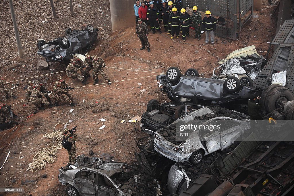 Rescuers try to move a car at the scene of the collapsed Yichang bridge near the city of Sanmenxia, central China's Henan province, on February 1, 2013 after a fireworks-laden truck exploded as it crossed the bridge killing 26 people as the structure collapsed and vehicles plummeted to the ground, state-run media reported. An 80-metre long part of the bridge collapsed and six vehicles had been retrieved from the debris, China's official news agency Xinhua said. The bridge near the city of Sanmenxia is on the G30 expressway, the longest road in China, which stretches for nearly 4,400 kilometres (2,700 miles) from China's western border with Kazakhstan to the eastern Yellow Sea.