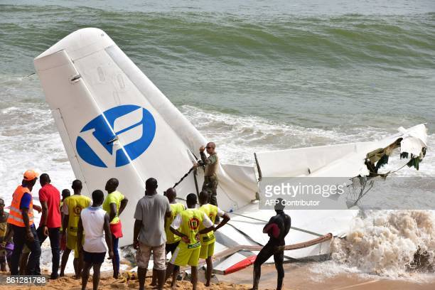 Rescuers try to pull out the wreckage of a cargo plane that crashed off Ivory Coast killing four on October 14 2017 at the PortBouet beach in Abidjan...