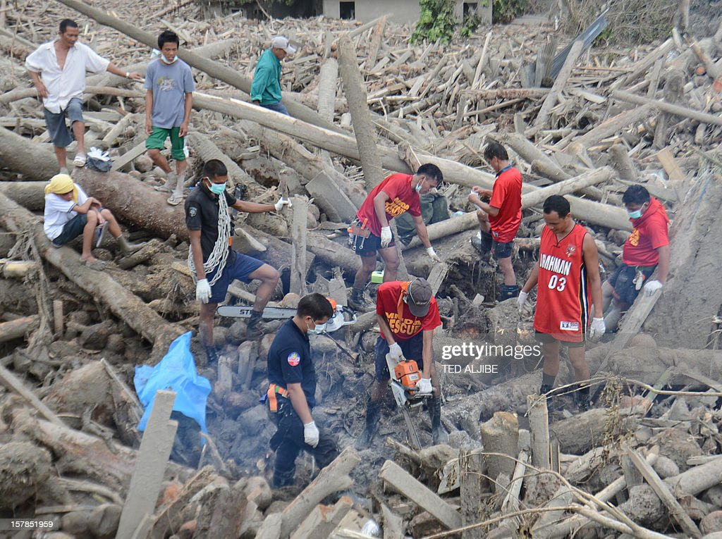 Rescuers use a chainsaw to cut logs as they look for dead bodies, victims of flash flooding at the height of Typhoon Bopha, during retrieval operation in New Bataan, Compostela Valley province on December 7, 2012. President Benigno Aquino vowed action on the Philippines' typhoon disasters December 7 as bruised and grieving survivors tried to recover from the latest that left nearly 500 people dead.