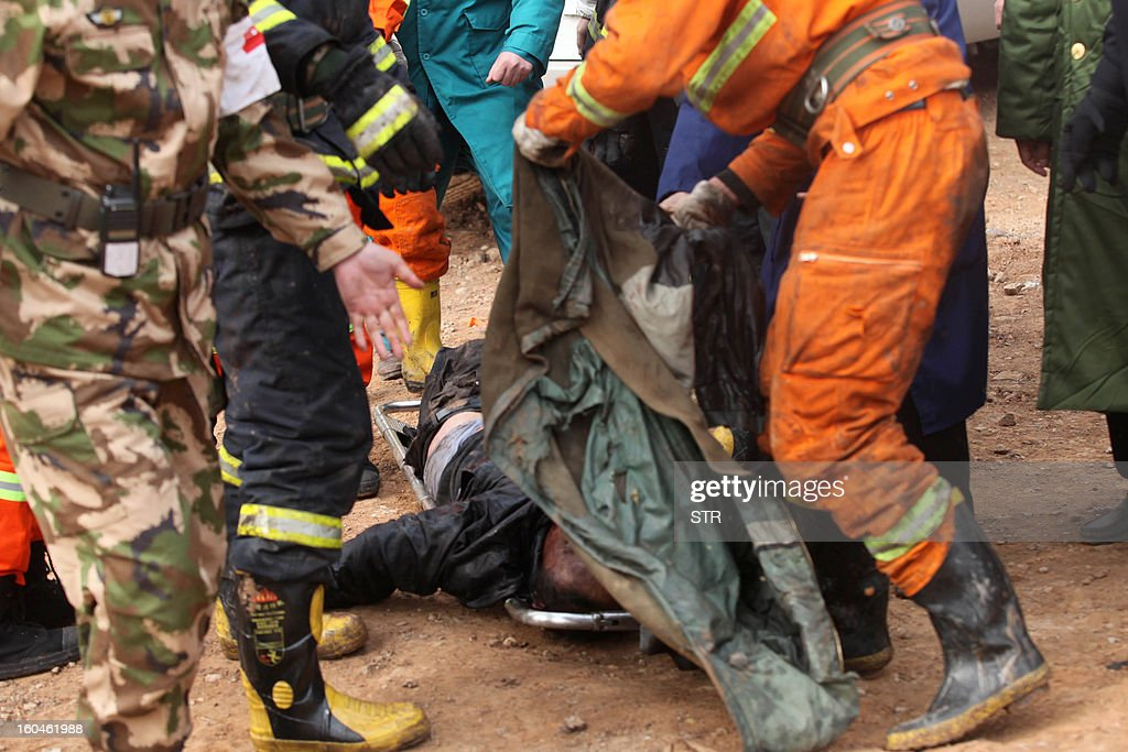 Rescuers use a coat to cover a dead body (C) at the scene of the collapsed Yichang bridge near the city of Sanmenxia, central China's Henan province, on February 1, 2013 after a fireworks-laden truck exploded as it crossed the bridge killing 26 people as the structure collapsed and vehicles plummeted to the ground, state-run media reported. An 80-metre long part of the bridge collapsed and six vehicles had been retrieved from the debris, China's official news agency Xinhua said. The bridge near the city of Sanmenxia is on the G30 expressway, the longest road in China, which stretches for nearly 4,400 kilometres (2,700 miles) from China's western border with Kazakhstan to the eastern Yellow Sea. AFP PHOTO CHINA OUT