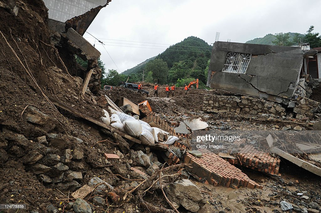 Rescuers walk past a destroyed house on July 28, 2013 in Tianshui, China. At least 22 people were killed and three others missing after rainstorm-triggered floods and landslides hit many places of Tianshui city recently.
